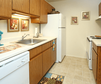 kitchen featuring refrigerator, dishwasher, ventilation hood, electric range oven, light tile floors, light countertops, and brown cabinetry, Fountain Park Westland