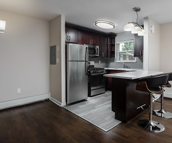 kitchen featuring a kitchen bar, a wealth of natural light, gas range oven, stainless steel refrigerator, baseboard radiator, microwave, dark brown cabinetry, dark parquet floors, light countertops, and pendant lighting, Pleasant View Gardens