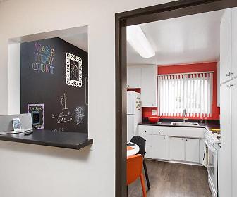 kitchen featuring natural light, gas range oven, light hardwood floors, white cabinetry, and dark countertops, AVA Burbank