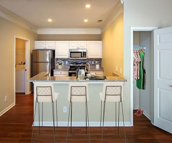 kitchen with a breakfast bar, washer / dryer, stainless steel refrigerator, range oven, microwave, stone countertops, white cabinets, and dark parquet floors, Christopher Wren Apartments