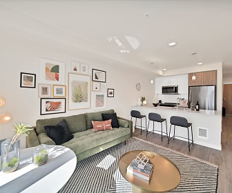 living room featuring parquet floors, a breakfast bar area, stainless steel refrigerator, and microwave, The Bower