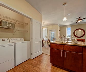 A full size washer and dryer in a closet with shelving adjacent to the kitchen, Le Mirage