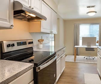 kitchen featuring natural light, electric range oven, stainless steel refrigerator, fume extractor, white cabinetry, light stone countertops, and light hardwood floors, eaves Tysons Corner