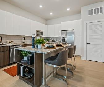 kitchen featuring a kitchen island, a kitchen bar, stainless steel appliances, light hardwood flooring, light stone countertops, and dark brown cabinets, Mirrorton Apartments