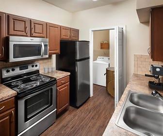 kitchen with stainless steel microwave, washer / dryer, refrigerator, electric range oven, light granite-like countertops, brown cabinets, and dark hardwood floors, Camden Buckingham