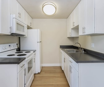 kitchen featuring electric range oven, microwave, white cabinetry, dark countertops, pendant lighting, and light parquet floors, Avenue Two