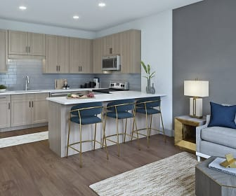 kitchen with a kitchen bar, stainless steel appliances, range oven, light brown cabinetry, light parquet floors, and light countertops, Alta Grand Crossing