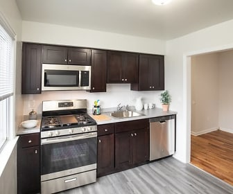 kitchen with stainless steel appliances, gas range oven, light hardwood floors, light countertops, and dark brown cabinets, Westgate Gardens