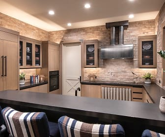 bar featuring a kitchen breakfast bar, oven, fume extractor, light countertops, and brown cabinetry, The Flin