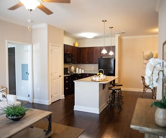 kitchen with a ceiling fan, refrigerator, microwave, range oven, white cabinetry, kitchen island sink, light countertops, dark hardwood floors, and pendant lighting, South Park Village Apartments