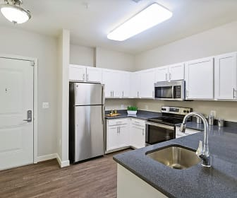 kitchen featuring electric range oven, stainless steel appliances, white cabinets, dark granite-like countertops, and light parquet floors, The Flats at Neabsco