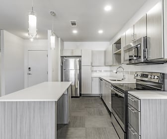 kitchen featuring a kitchen island, electric range oven, stainless steel appliances, light brown cabinetry, light countertops, pendant lighting, and dark floors, Pinnacle Heights