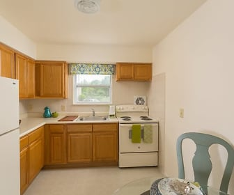 kitchen with natural light, refrigerator, electric range oven, light tile floors, brown cabinets, and light countertops, Mansfield Village Apartments