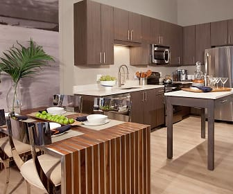 kitchen with a kitchen breakfast bar, stainless steel appliances, range oven, light countertops, dark brown cabinetry, and light hardwood flooring, Avalon Potomac Yard