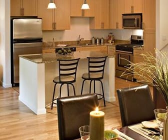 kitchen featuring microwave, stainless steel refrigerator, range oven, dark countertops, brown cabinets, and light hardwood floors, Avalon White Plains