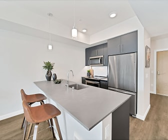 kitchen with a breakfast bar, a kitchen island, stainless steel appliances, range oven, dark brown cabinetry, light countertops, pendant lighting, and dark hardwood floors, The Bower