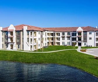 view of property featuring an expansive lawn, Estero Parc Apartments