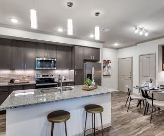 kitchen with stainless steel appliances, range oven, dark brown cabinets, pendant lighting, light stone countertops, and light parquet floors, The Park at Tour 18