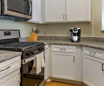 kitchen featuring gas range oven, stainless steel appliances, light granite-like countertops, white cabinetry, and light parquet floors, Avalon Russett