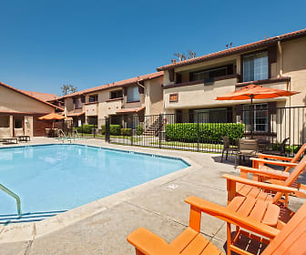 Swimming pool with lounge chairs surrounded by apartment building., Devonshire Apartments