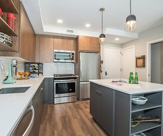 kitchen featuring stainless steel appliances, range oven, light countertops, dark hardwood floors, a center island with sink, pendant lighting, and dark brown cabinets, RiverHouse 9 at Port Imperial