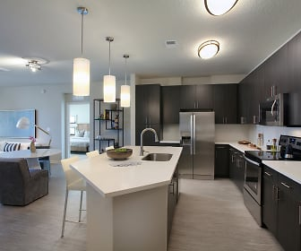 kitchen with a kitchen island, electric range oven, stainless steel refrigerator, microwave, light floors, dark brown cabinetry, light countertops, and pendant lighting, Legacy Union Square