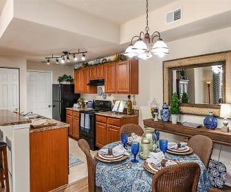 kitchen featuring range oven, refrigerator, fume extractor, dark granite-like countertops, light flooring, and brown cabinets, Fountain Villas