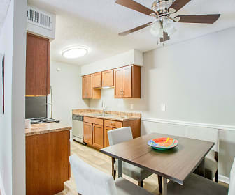 kitchen with a ceiling fan, dishwasher, stone countertops, light floors, and brown cabinetry, Bradford Woods
