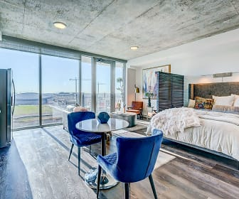 Stunning open kitchen and living room concept with stainless steel appliances, wood plank flooring, pendant lighting and quartz countertops, Skyhouse Frisco Station