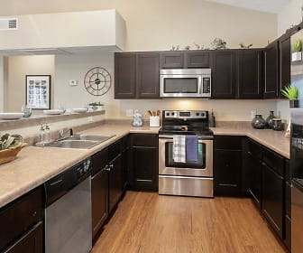 kitchen featuring lofted ceiling, stainless steel appliances, electric range oven, dark brown cabinetry, light granite-like countertops, and light hardwood floors, The Social Campus