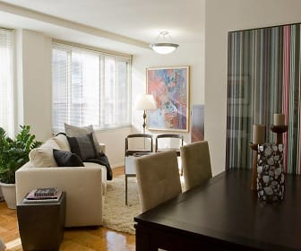 Studio apartment space accommodates both a living room area with a sofa and side tables as well as a dining room area with a standard-size dining table, The Statesman