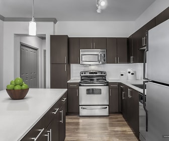 kitchen featuring a kitchen island, refrigerator, dishwasher, electric range oven, stainless steel microwave, pendant lighting, light parquet floors, and dark brown cabinetry, Camden Asbury Village