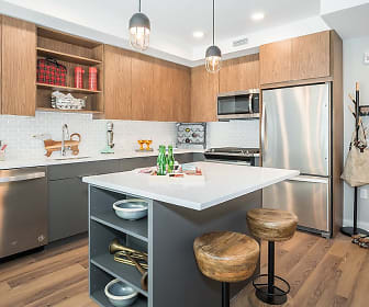 kitchen featuring a breakfast bar, a kitchen island, stainless steel appliances, range oven, dark brown cabinets, light countertops, pendant lighting, and light hardwood flooring, RiverHouse 9 at Port Imperial