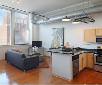 kitchen with plenty of natural light, electric range oven, dishwasher, TV, stainless steel microwave, dark countertops, light hardwood flooring, light brown cabinetry, and pendant lighting, Boston Lofts