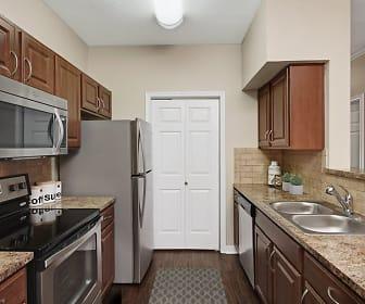 kitchen featuring refrigerator, dishwasher, electric range oven, stainless steel microwave, dark parquet floors, light granite-like countertops, and dark brown cabinets, Camden Buckingham