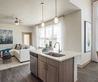 kitchen featuring plenty of natural light, a ceiling fan, a kitchen island, stainless steel dishwasher, pendant lighting, dark brown cabinetry, dark hardwood floors, and light countertops, Avalon Southlands