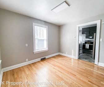 empty room with hardwood floors, natural light, and range oven, JEK Homes