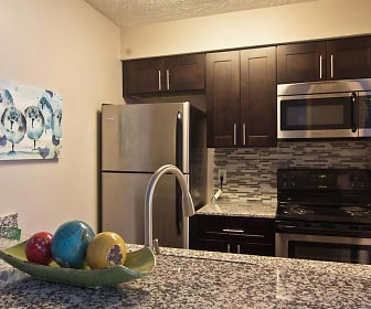 kitchen featuring stainless steel appliances, electric range oven, granite-like countertops, and dark brown cabinets, Camelot East