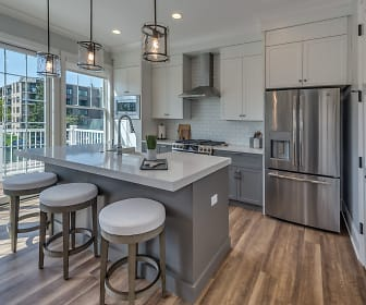 kitchen with a healthy amount of sunlight, a breakfast bar area, stainless steel appliances, ventilation hood, white cabinetry, light countertops, kitchen island sink, light floors, and pendant lighting, Eldridge Townhomes