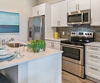 kitchen featuring a kitchen breakfast bar, stainless steel appliances, electric range oven, white cabinets, light parquet floors, and light countertops, Pines Garden at City Center