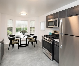 kitchen featuring carpet, natural light, gas range oven, TV, stainless steel appliances, light floors, light granite-like countertops, and dark brown cabinets, Crown Court