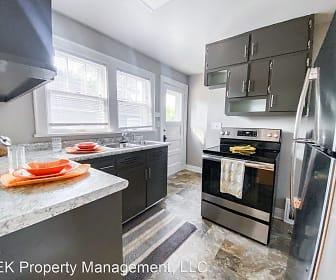 kitchen with plenty of natural light, range hood, stainless steel refrigerator, electric range oven, light tile floors, dark brown cabinets, and light countertops, JEK Homes