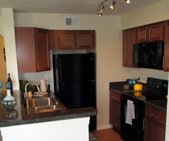 kitchen featuring refrigerator, electric range oven, microwave, dark flooring, dark stone countertops, and dark brown cabinets, TGM Bermuda Island