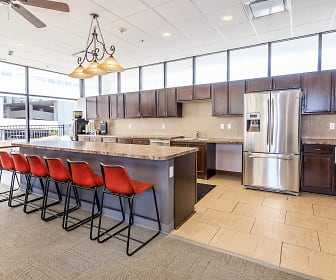kitchen with a breakfast bar, natural light, a ceiling fan, stainless steel refrigerator, pendant lighting, light tile flooring, light granite-like countertops, and dark brown cabinets, Walnut Tower