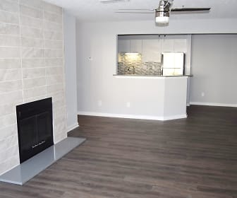 Interior view of renovated apartment with wood inspired plank flooring, fireplace with large ceramic tiles to the ceiling and view into kitchen, Decatur Flats