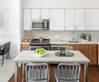 kitchen featuring carpet, stainless steel microwave, refrigerator, electric range oven, light floors, light countertops, and white cabinetry, The Merc at Moody and Main