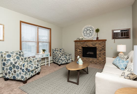 carpeted living room with a fireplace, natural light, and baseboard radiator, Creekstone Falls