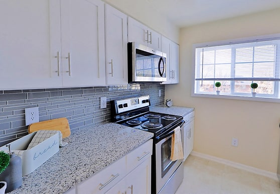 kitchen with natural light, dishwasher, electric range oven, stainless steel microwave, light tile floors, white cabinetry, and light granite-like countertops, Mount Vernon Square Apartments