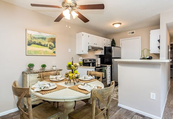 dining area featuring a ceiling fan, hardwood flooring, refrigerator, range oven, and exhaust hood, Hilliard Station Apartments
