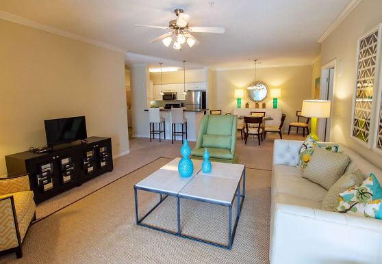 carpeted living room featuring a ceiling fan, a breakfast bar, refrigerator, TV, and microwave, Sugar Mill